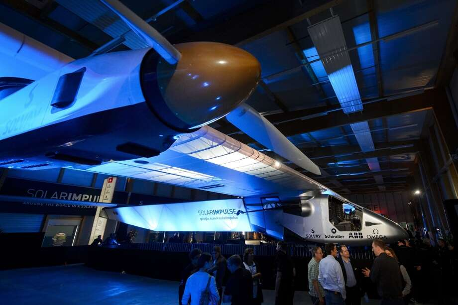 People look at the Solar Impulse 2 solar-powered plane to be used for a round-the-world voyage next year, during its unveiling in Payerne, on April 9, 2014. Photo: FABRICE COFFRINI, AFP/Getty Images