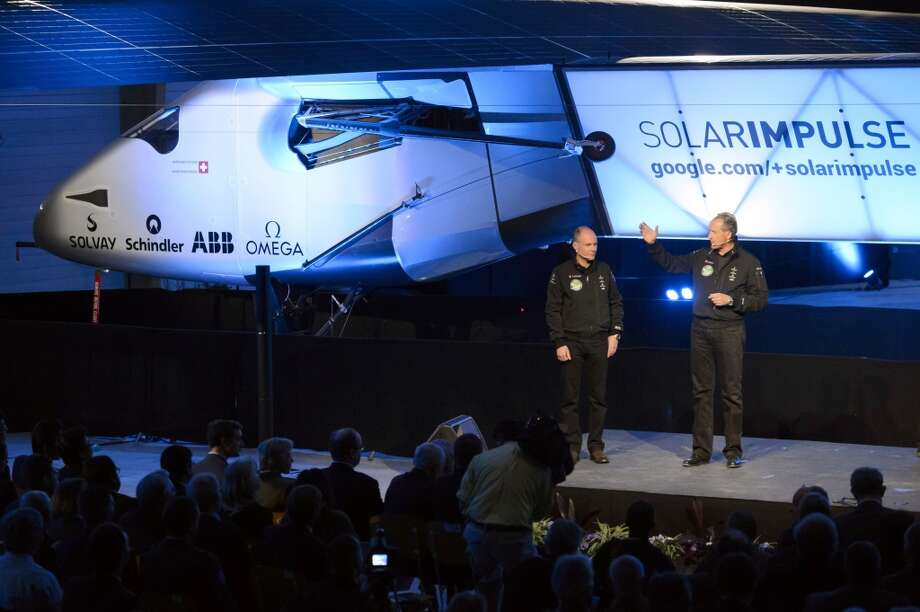 "Solar Impulse's CEO and pilot Andre Borschberg (right) and Solar Impulse's founder, chairman and pilot Bertrand Piccard (left) speak in front of the new experimental aircraft ""Solar Impulse 2"", during the official unveiling at the airbase in Payerne, Switzerland, Wednesday, April 9, 2014. Photo: Laurent Gillieron, Associated Press"