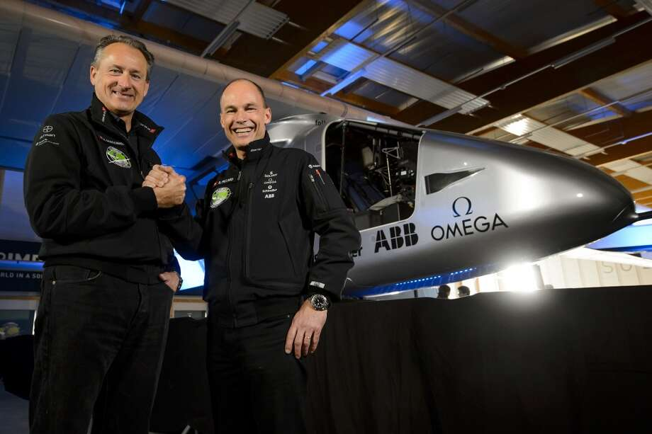Swiss pilots Bertrand Piccard (left) and Andre Borschberg, who flew the Solar Impulse experimental solar-powered plane on a transcontinental trip, pose in front of their second solar-powered plane, which they aim to take on a round-the-world voyage next year. Photo: FABRICE COFFRINI, AFP/Getty Images