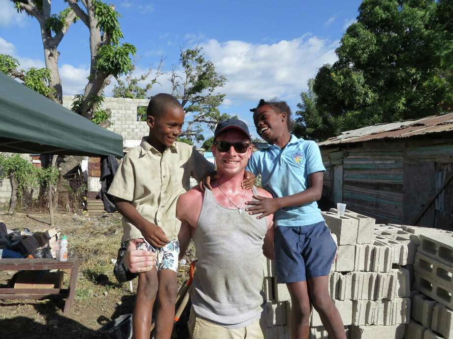 Phil Morehouse, of First Congregational Church of Darien, who recently went on a mission trip to the Dominican Republic. Morehosue obtained a couple of new friends. Photo: Contributed Photo, Contributed / Darien News