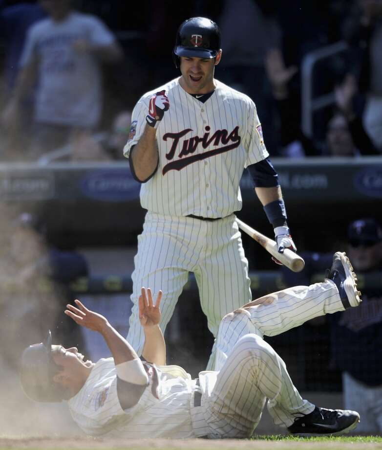 Kurt Suzuki #8 of the Minnesota Twins rolls after a sliding in safely to home plate against the Oakland Athletics as teammate Joe Mauer #7 looks on during the ninth inning of the game on April 9, 2014 at Target Field in Minneapolis, Minnesota. Photo: Hannah Foslien, Getty Images