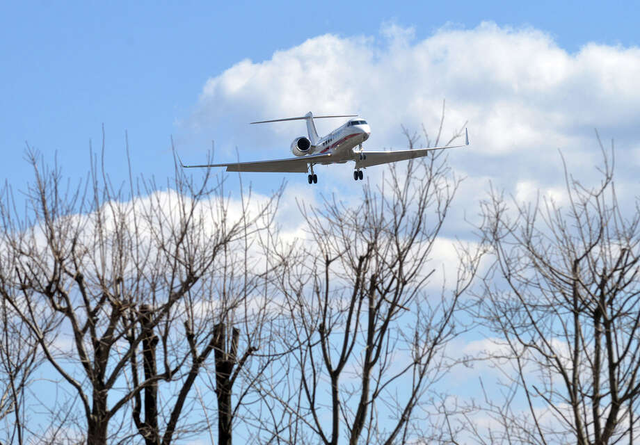 "A jet plane lands at Westchester County Airport in White Plains, N.Y., Wednesday, April 9, 2014. Trees in Greenwich have inched their way into a designated ""clear zone"" in the skies above the airport. Planes must travel through this zone on their final landing approach so the FAA is considering shortening the usable length of the alternate runway again. Photo: Bob Luckey / Greenwich Time"