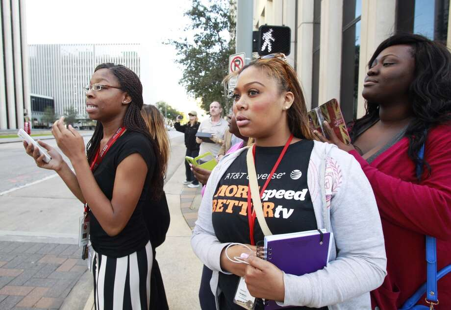 Shonty Hubbard, left, Ashlee Jones and Olu Shoyinka stand at the corner of Jefferson and Smith, hoping to get a glimpse of the president. Photo: Melissa Phillip, Chronicle
