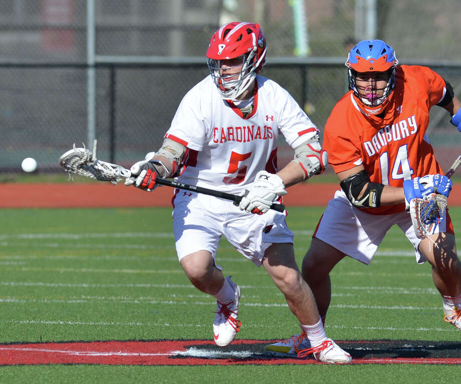 At left, Michael Sullivan (#5) of Greenwich goes for the ball as Danbury's Eric Henry (#14) pursues during the boys high school lacrosse match between Greenwich High School and Danbury High School at Greenwich, Wednesday, April 9, 2014. Greenwich won the match, 19-3. Photo: Bob Luckey / Greenwich Time