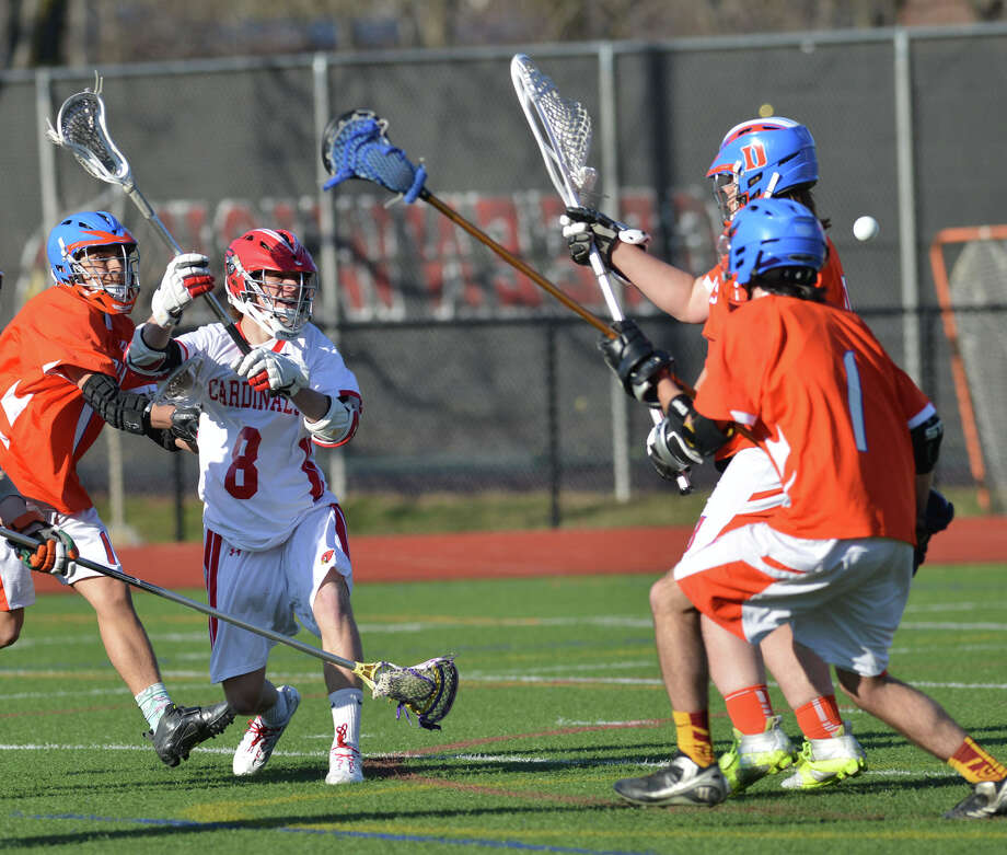 Second from left, John Tooher (#8) of Greenwich shoots and scores during the high school lacrosse match between Greenwich High School and Danbury High School at Greenwich, Wednesday, April 9, 2014. Greenwich won the match, 19-3. Photo: Bob Luckey / Greenwich Time