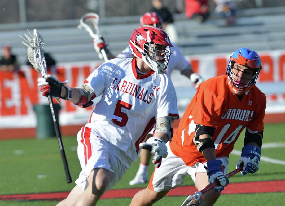 At left, Michael Sullivan (#5) of Greenwich attempts to get past Danbury defender, Eric Henry (#14), during the boys high school lacrosse match between Greenwich High School and Danbury High School at Greenwich, Wednesday, April 9, 2014. Greenwich won the match, 19-3. Photo: Bob Luckey / Greenwich Time