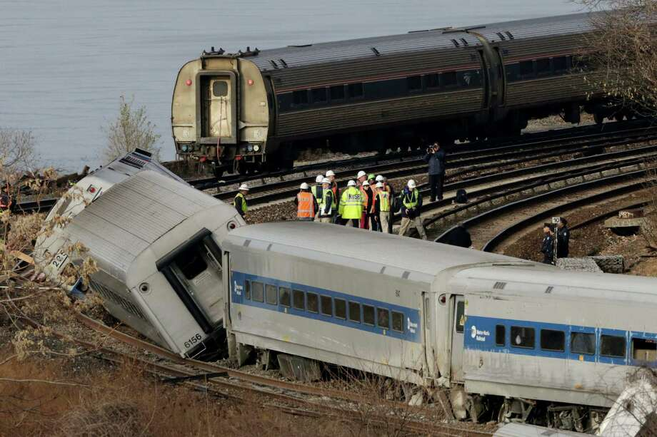 FILE- In this Dec. 1, 2013 file photo, an Amtrak train, top, traveling on an unaffected track, passes a derailed Metro-North commuter train in the Bronx borough of New York. Metro-North trains are equipped with an automatic breaking system that might have prevented the crash, but it was configured to mainly to keep trains at a safe distance from one another, not to enforce speed limits on curves, hills or bridges. Four people died when the Metro-North commuter train failed to slow as it approached a tight curve in the Bronx. (AP Photo/Mark Lennihan, File) ORG XMIT: NYR402 Photo: Mark Lennihan / AP