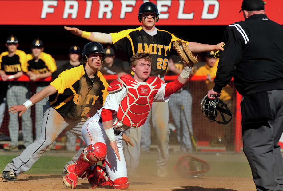 Fairfield Prep catcher Jake Berry and Amity players Sebastian DiMauro and Anthony Capozziello, left, who slid into home plate, look to the call by the umpire, during opening day baseball action at Fairfield University in Fairfield, Conn. on Wednesday April 9, 2014. Capozziello was called out. Photo: Christian Abraham / Connecticut Post