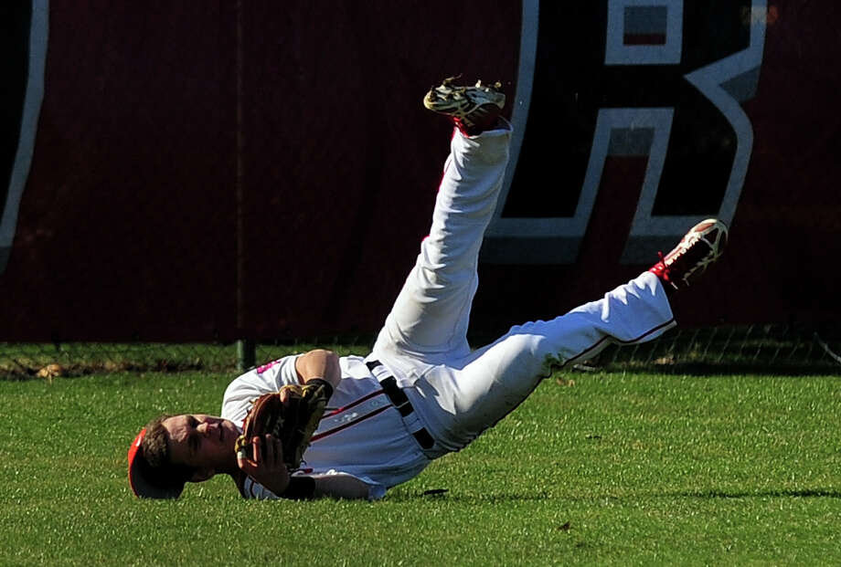 Fairfield Prep's Brett Stevenson starts to go into a tumble after making a catch in left field, during opening day baseball action against Amity at Fairfield University in Fairfield, Conn. on Wednesday April 9, 2014. Photo: Christian Abraham / Connecticut Post