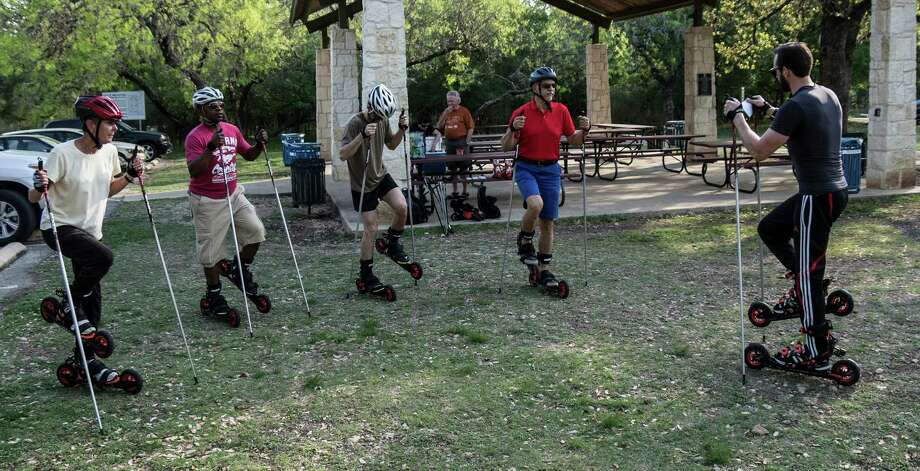 Philipp Dmitriev (far right) leads roller skiers in warm up exercises to get them used to being on roller skis before taking to the road.