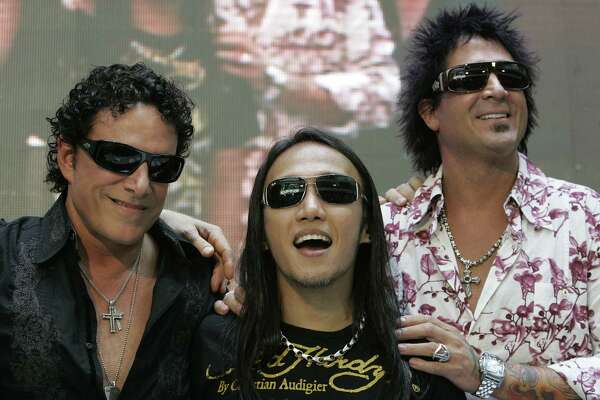 """FILE - In this March 2, 2009 file photo, Filipino singer-songwriter Arnel Pineda, center, the lead vocalist of American rock band """"Journey"""" smiles beside bandmates Neal Schon, left, and Deen Castronovo, right, during a press conference at a mall in suburban Quezon City, north of Manila, Philippines. American rock band Journey's lead vocalist Pineda said he's been putting together an album of his own compositions in his own voice which he plans to release in 2014. The singer spoke in an interview Tuesday, April 8, 2014,  during the launch of his version of the song """"Charity"""" in the animated children's music video Cha-Ching on Cartoon Network. (AP Photo/Aaron Favila, File) ORG XMIT: TOK104"""