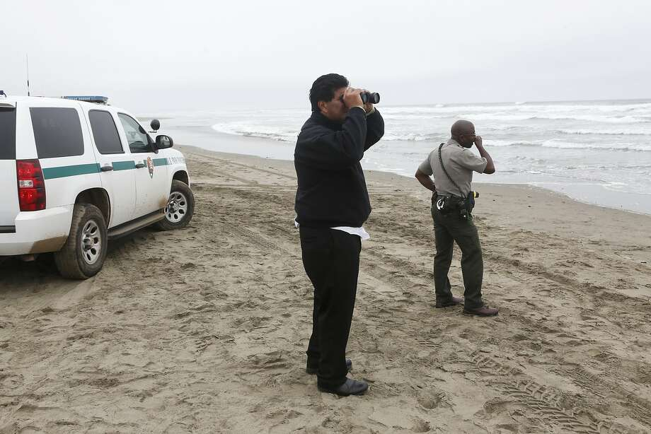 Emergency workers on Ocean Beach search for a 14-year-old boy who was swept out to sea. Photo: Beck Diefenbach, Special To The Chronicle