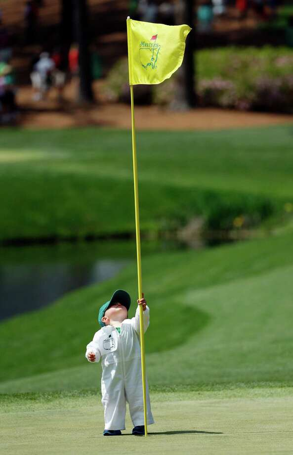 "Tending the flag is a tall order for 14-month-old Finn Stallings, who ""caddied"" for his father, Scott, during the Par-3 Contest on Wednesday. Photo: Matt Slocum, STF / AP"
