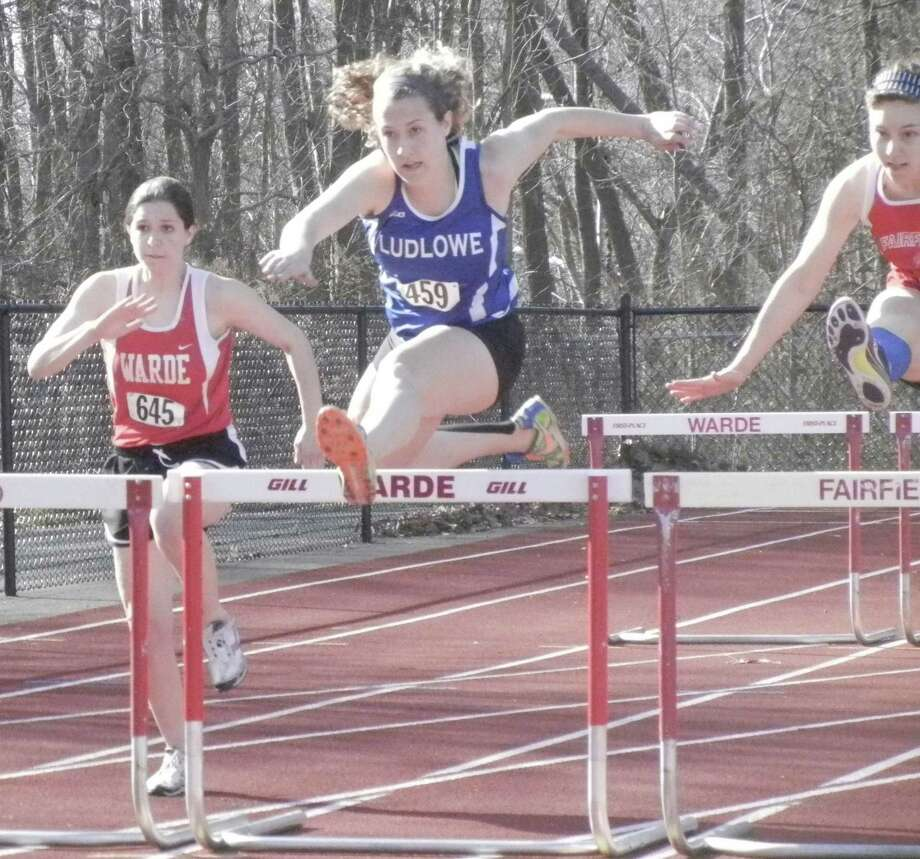 Fairfield Ludlowe senior Alex Wykoff, center, on her way to victory in the 100-meter hurdles on Wednesday, April 9 at Fairfield Warde. The Mustangs beat the Falcons 91-54. Wykoff also won the 300 hurdles and was part of the winning 4-by-400-meter relay. Photo: Reid L. Walmark / Fairfield Citizen