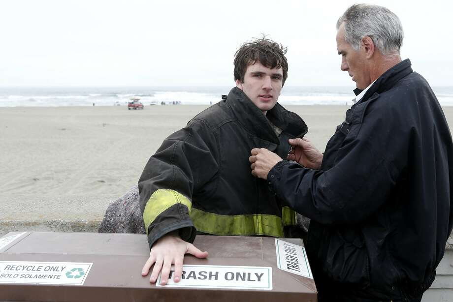 S.F. fire Capt. Joe Barbero puts his jacket on his son, Tony, who rescued two people Wednesday at Ocean Beach. Photo: Beck Diefenbach, Special To The Chronicle
