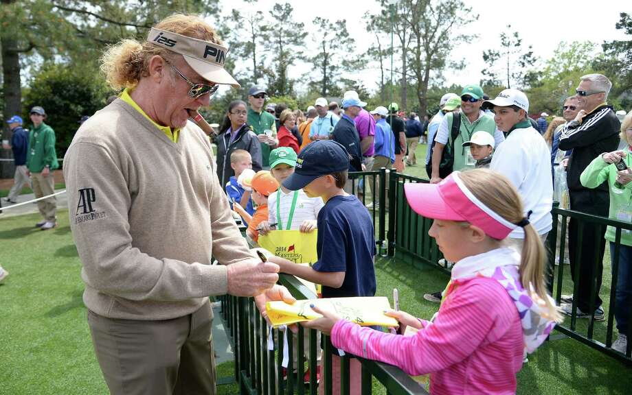 Miguel Angel Jimenez, 50, signing an autograph for a young fan at Augusta National, is one of the Masters' elder statesmen. Photo: Harry How / Getty Images / 2014 Getty Images