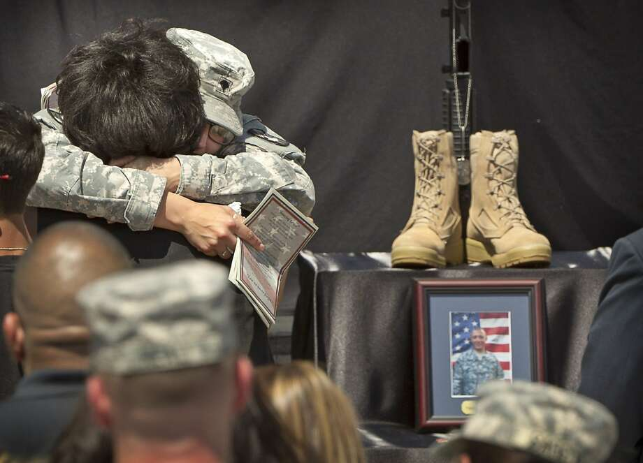 Spc. Kristen Haley, left, the fiancee of Sgt. First Class Daniel Ferguson who was killed in the Fort Hood shooting, is consoled at the memorial ceremony for the victims of the Fort Hood shooting at Fort Hood, Texas, on Wednesday April 9, 2014.   (AP Photo/Austin American-Statesman, Jay Janner) AUSTIN CHRONICLE OUT, COMMUNITY IMPACT OUT; INTERNET AND TV MUST CREDIT PHOTOGRAPHER AND STATESMAN.COM; MAGS OUT Photo: Jay Janner, Associated Press