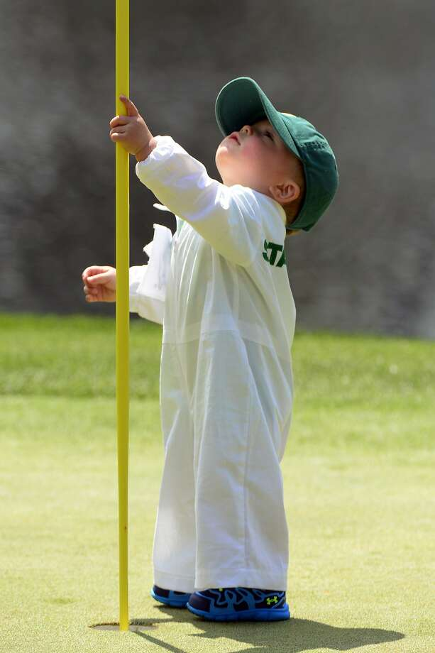 Apr 9, 2014; Augusta, GA, USA; Finn Stallings the son of Scott Stallings plays with the flag stick on the 4th green during the Par 3 Contest before the 2014 The Masters golf tournament at Augusta National Golf Club. Mandatory Credit:  Michael Madrid-USA TODAY Sports Photo: Michael Madrid, Reuters
