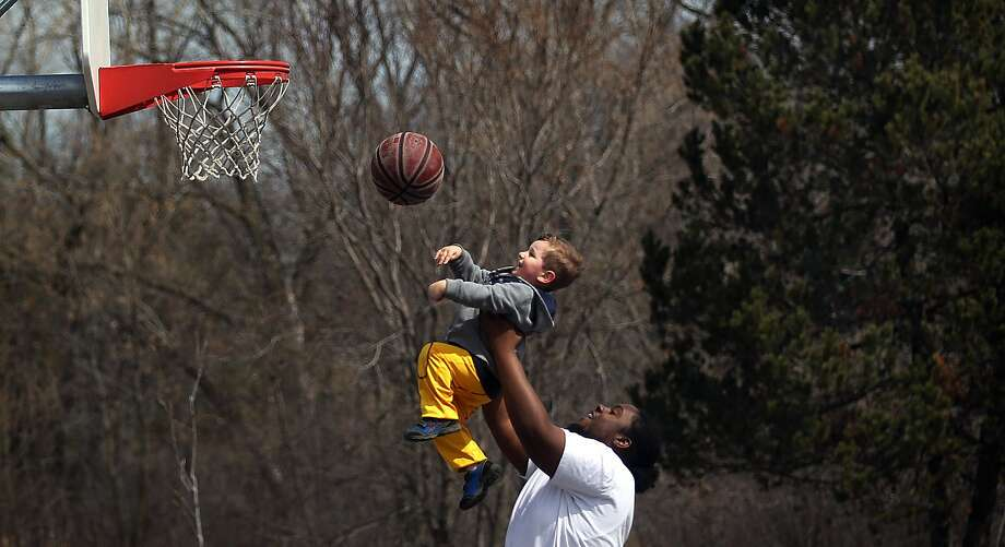 Assist on the basket:Demetri Collins-Brooks helps 2-year-old Dylan Bauer with his layup at Theodore Wirth Park