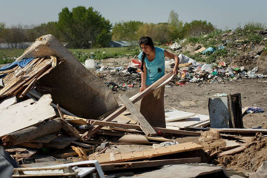 MADRID, SPAIN - APRIL 09:  A woman searches for her belongings under the debris of her hut after it was demolished at 'el Gallinero' on April 9, 2014 in Madrid, Spain. Madrid Council sent bulldozers escorted by police to demolish some makeshift structures in the Gallinero's shanty town on the outskirts of Madrid , a day after 'International Roma Day'. The Gallinero slum is home to a group of Romanian Gypsies who live in precarious conditions with no running water, and who were allowed to remove some of their belongings before their homes were destroyed.  (Photo by Pablo Blazquez Dominguez/Getty Images) *** BESTPIX *** Photo: Pablo Blazquez Dominguez, Getty Images