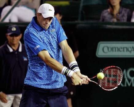 John Isner, of the United States, hits a return to Dustin Brown, of Germany, at the U.S. Men's Clay Court Championship tennis tournament, Wednesday, April 9, 2014, in Houston. (AP Photo/Houston Chronicle, Bob Levey) MANDATORY CREDIT Photo: Bob Levey, Associated Press / Houston Chronicle
