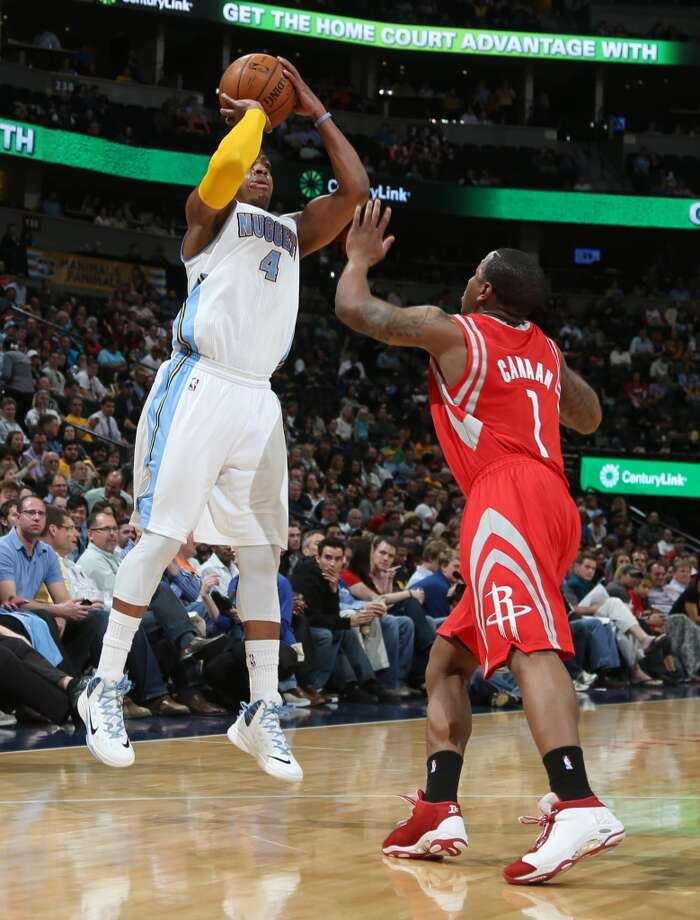 Nuggets guard Randy Foye, left, launches a three-point basket over Rockets guard Isaiah Canaan. Photo: David Zalubowski, Associated Press