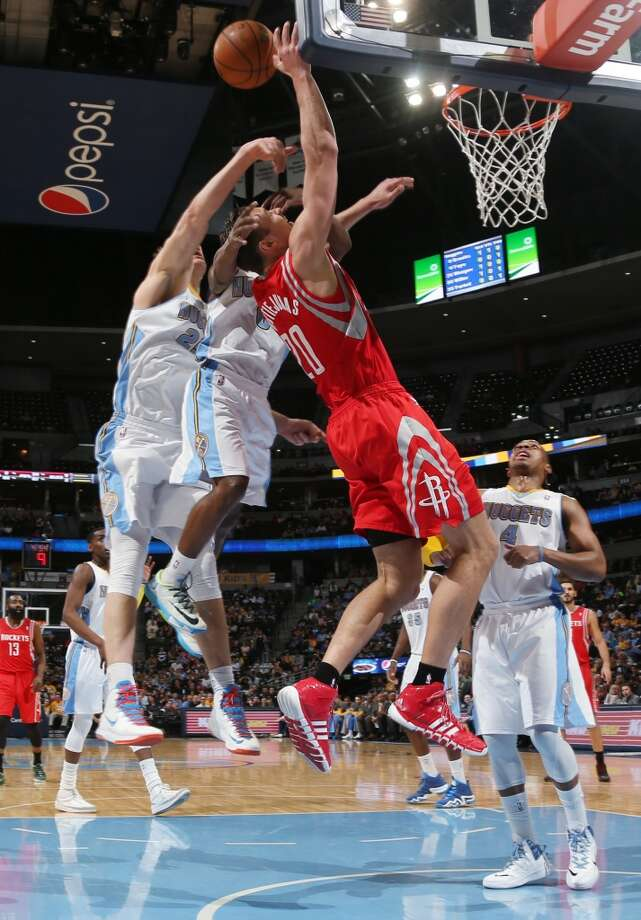 Rockets forward Donatas Motiejunas, third from left, of Lithuania, is fouled as he goes up for a shot by Nuggets guard Aaron Brooks, second from left, and center Timoey Mozgov, of Russia, left, as guard Randy Foye, right, looks on. Photo: David Zalubowski, Associated Press