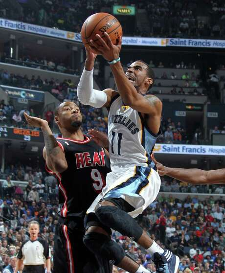 Memphis' Mike Conley soars toward the basket against Miami's Rashard Lewis on Wednesday. Conley scored 26 points in the Grizzlies' victory. Photo: Nikki Boertman / McClatchy-Tribune News Service / The Commercial Appeal