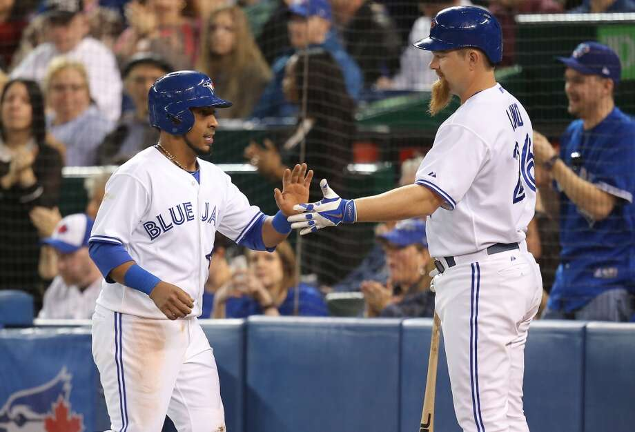 Maicer Izturis of the Blue Jays is congratulated by Adam Lind after scoring a run. Photo: Tom Szczerbowski, Getty Images