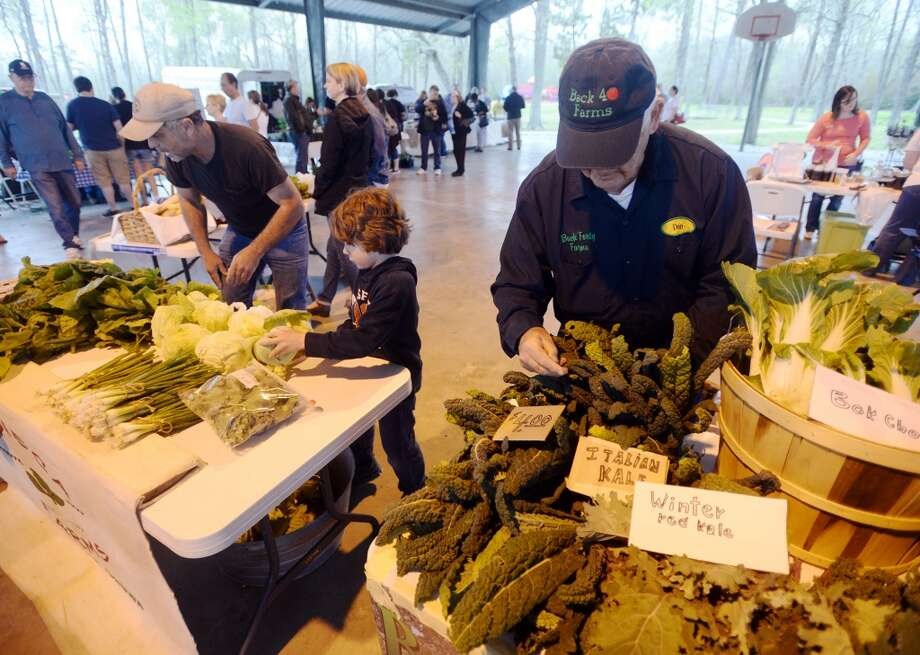 Bobby Sisk and Easton Evans, 6, from left, tend to the Resveca Farms table, while Don Socher, right, looks over the produce on the Back 40 Farms table Saturday morning. The Beaumont Farmer's Market opened for business at the Beaumont Athletic Complex on Saturday morning. Photo taken Saturday, 3/15/14 Jake Daniels/@JakeD_in_SETX