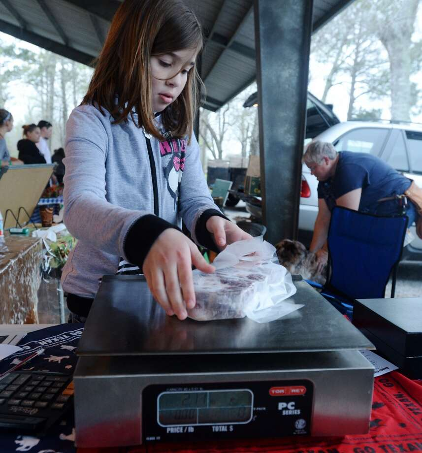 Emily Ogden weighs a package of beef at the Gentz Cattle Company table Saturday morning. The Beaumont Farmer's Market opened for business at the Beaumont Athletic Complex on Saturday morning. Photo taken Saturday, 3/15/14 Jake Daniels/@JakeD_in_SETX