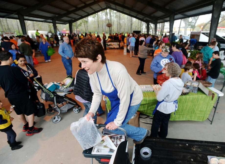 Kathryn Smith climbs down from the back of a pickup truck with a bag of blueberries Saturday morning. The Beaumont Farmer's Market opened for business at the Beaumont Athletic Complex on Saturday morning. Photo taken Saturday, 3/15/14 Jake Daniels/@JakeD_in_SETX