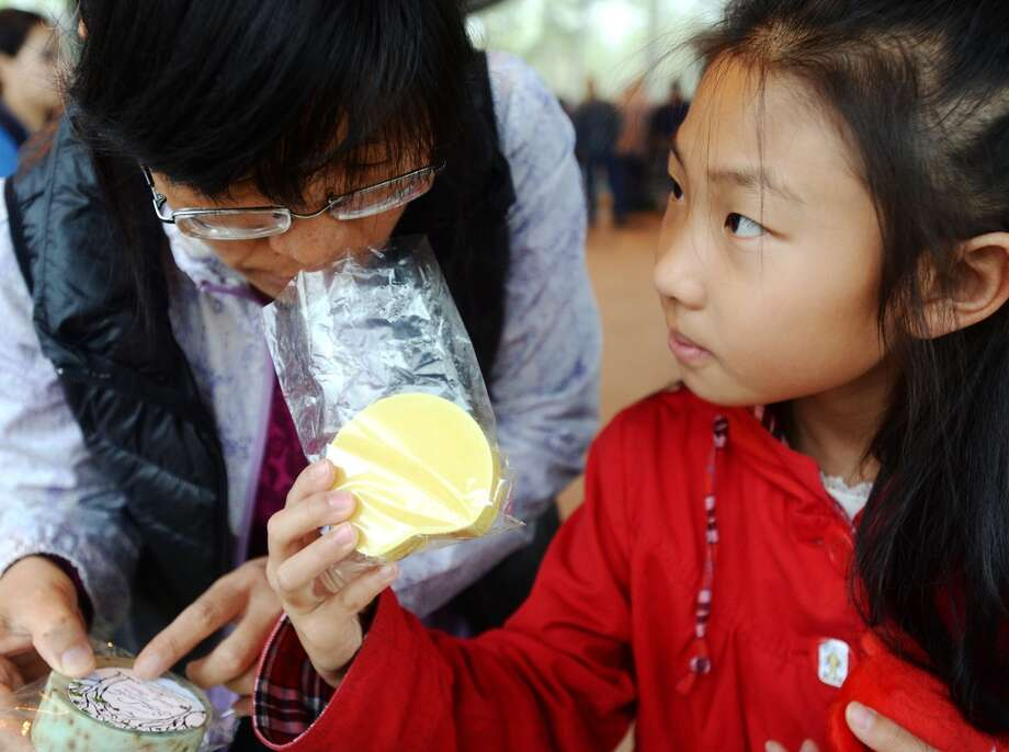 Xiao Ying Bi smells soap held by Sarah Wang, 10, during Saturday's market. The Beaumont Farmer's Market opened for business at the Beaumont Athletic Complex on Saturday morning. Photo taken Saturday, 3/15/14 Jake Daniels/@JakeD_in_SETX