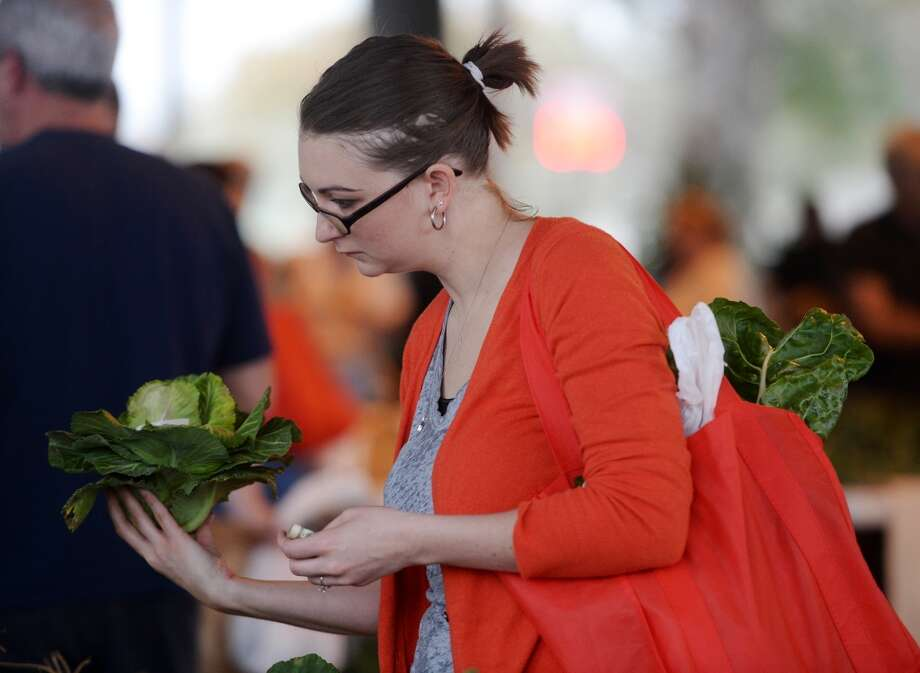 Ariane Williams checks out a cabbage during Saturday's market. The Beaumont Farmer's Market opened for business at the Beaumont Athletic Complex on Saturday morning. Photo taken Saturday, 3/15/14 Jake Daniels/@JakeD_in_SETX