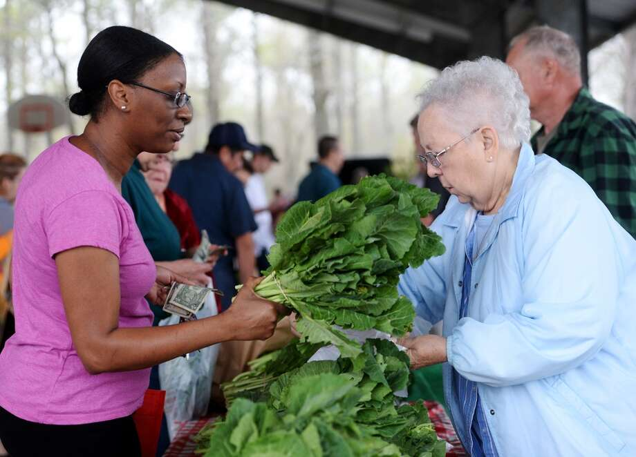 Tonya Hockless, left, buys some fresh vegetables from Tessie Alvarez at the Garnet's Garden table Saturday. The Beaumont Farmer's Market opened for business at the Beaumont Athletic Complex on Saturday morning. Photo taken Saturday, 3/15/14 Jake Daniels/@JakeD_in_SETX
