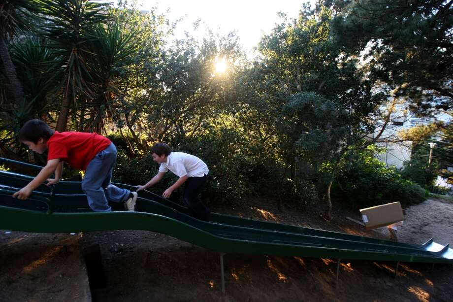 The Winfield Street slides are entirely hidden by trees. This steep joy ride can be found near Winfield Street and Esmeralda Avenue in Bernal Heights. Pictured: 8-year-old Darragh Long (left) and 8-year-old Michael Cordobes (right),  from San Francisco walk up the slides on January 15, 2009. Google map Photo: Liz Hafalia, The Chronicle