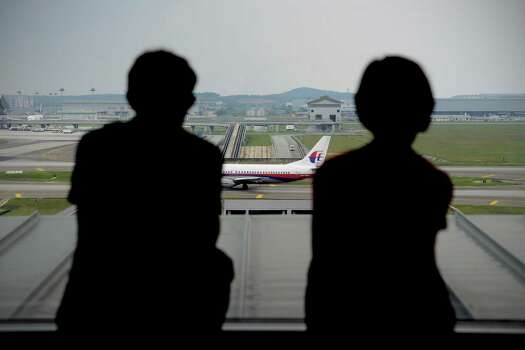 A couple is silhouetted as they watch a Malaysia Airlines plane on the tarmac from the viewing gallery at Kuala Lumpur International Airport in Sepang, Malaysia, Thursday, April 10, 2014. With hopes high that search crews are zeroing in on the missing Malaysian jetliner's crash site, ships and planes hunting for the aircraft intensified their search efforts on Thursday after equipment picked up sounds consistent with a plane's black box in the deep waters of the Indian Ocean. Photo: Joshua Paul, AP / AP