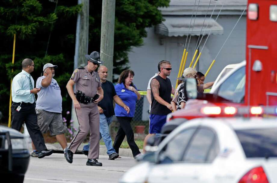 A Florida state trooper, center, escorts a group of parents to a day care center to pick up their children after a vehicle crashed into the center, Wednesday, April 9, 2014, in Winter Park, Fla. At least 15 people were injured, including children. Photo: John Raoux, AP / AP
