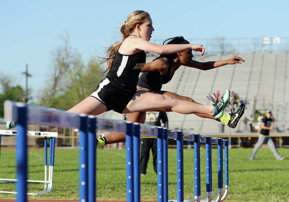 Nederland's Kinsey Miller, front, and Central's Paizley Armstrong compete in the 300 meter hurdles during Wednesday's track finals. The District 20-4A Varsity Track Meet finals were held Wednesday afternoon at Babe Zaharias Stadium.