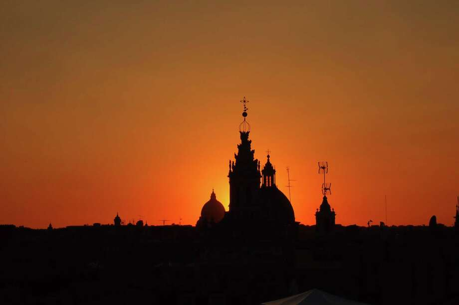 The domes and rooftops of Rome in sunset silhouettte, including the spiraling tower of Sant'Ivo alla Spaienza in the foreground and St. Peter's Basicala in the back. Photo: Andrew Sessa / Andrew Sessa