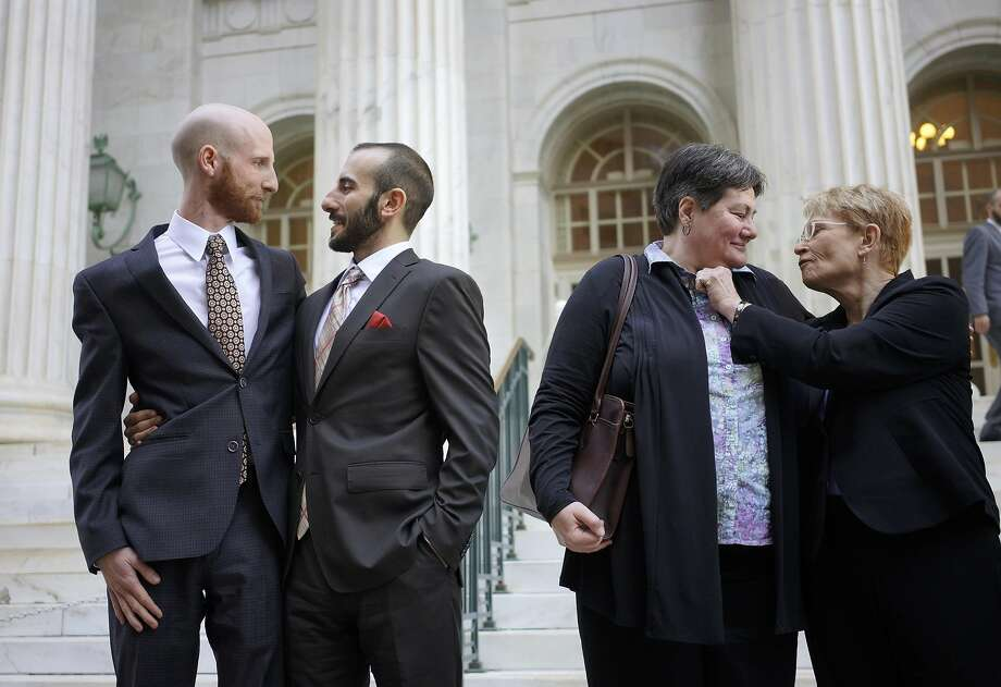 Lead plaintiffs Derek Kitchen (left) and Moudi Sbeity and plaintiffs Kate Call and Karen Archer appear outside the courthouse after a federal appeals panel in Denver heard arguments on the Utah ban. Photo: Rick Wilking, Reuters