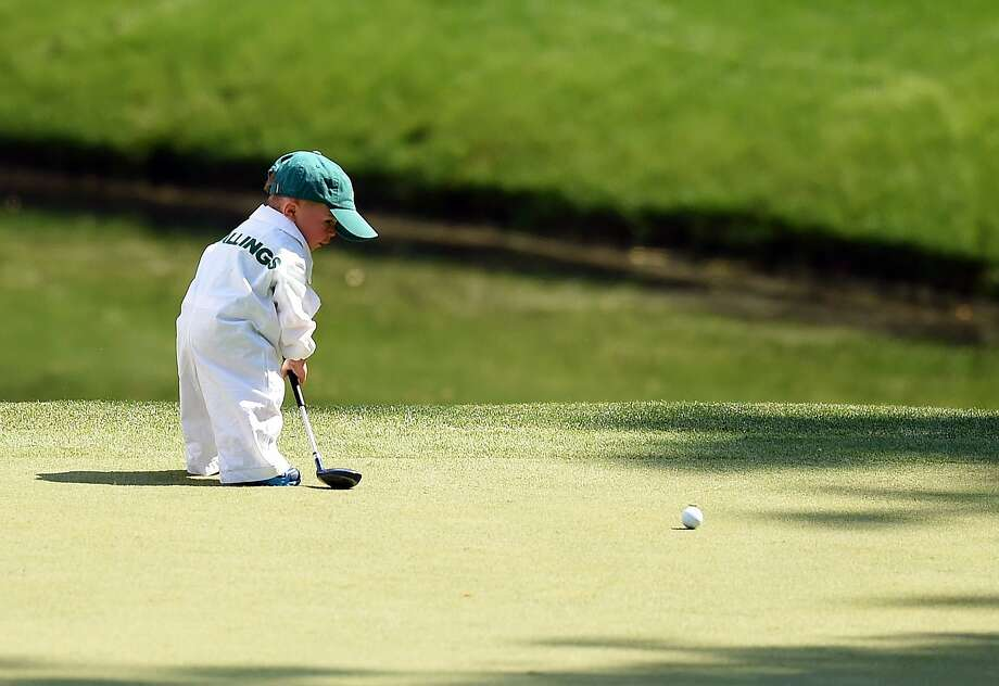 Already a 7 handicap:Finn, the son of Scott Stallings, attempts to drain a putt at the Masters in Augusta, Ga. Photo: Jim Watson, AFP/Getty Images
