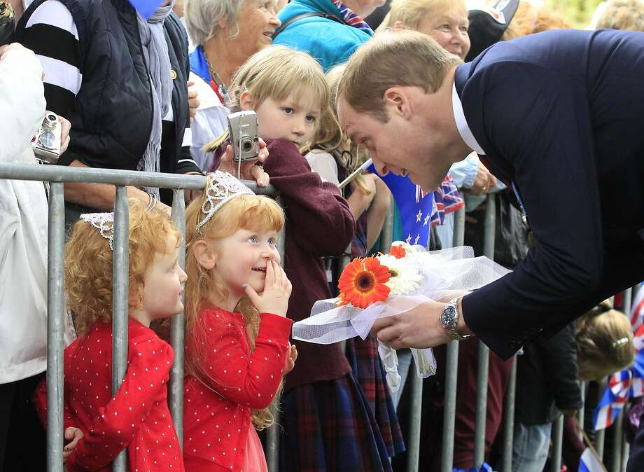 A present from the princesses:Prince William receives flowers from 3-year-old   tiara twins Lola and Milly Barnett during a walkabout in Seymour Square in Blenheim, New Zealand. Photo: Derek Flynn, AFP/Getty Images