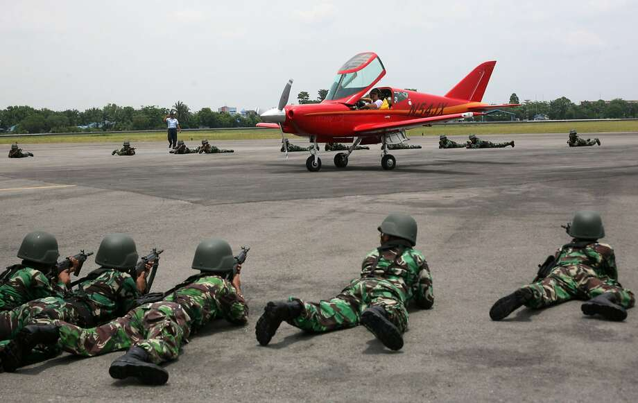Indonesian soldiers train their weapons at an airplane piloted by 65 year-old Heinz Peier of Switzerland after it was intercepted by Indonesian jet fighters and forced to land at Soewondo Air Base in Medan, North Sumatra, Indonesia, Thursday, April 10, 2014. Peier was on a ferry flight from Colombo to Singapore when he entered Indonesian airspace illegally, an Air Force official said.  (AP Photo/Binsar Bakkara) Photo: Binsar Bakkara, Associated Press
