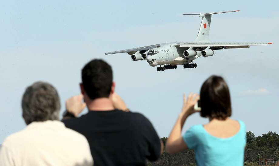 Spectators take photos of a Chinese  Ilyushin IL-76 aircraft as it comes in for a landing at Perth International Airport after returning from the ongoing search operations for missing Malaysia Airlines Flight 370 in Perth,  Australia, Thursday, April 10, 2014. With hopes high that search crews are zeroing in on the missing Malaysian jetliner's crash site, ships and planes hunting for the aircraft intensified their efforts Thursday after equipment picked up sounds consistent with a plane's black box in the deep waters of the Indian Ocean.  (AP Photo/Rob Griffith) Photo: Rob Griffith, Associated Press