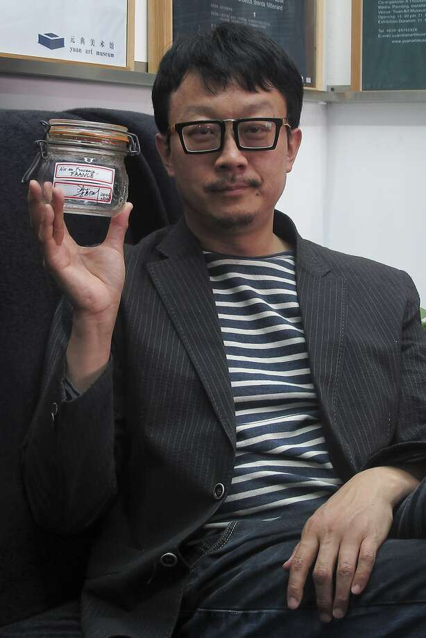 Artist Liang Kegang poses in Beijing with a jar of mountain air collected in Provence, France. Photo: Didi Tang, Associated Press