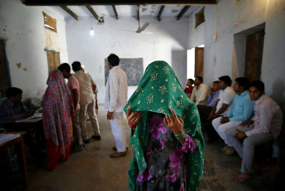 A woman holds a veil over her face and waits for her identity card to be checked before she is allowed to vote in Chandeni, in the northern Indian state of Haryana, Thursday, April 10, 2014. Indians voted in the crucial third phase of national elections Thursday, with millions going to the polls in the heartland states that are essential to the main opposition Hindu nationalist party's bid to end the 10-year rule of Congress party. (AP Photo/Saurabh Das) Photo: Saurabh Das, Associated Press