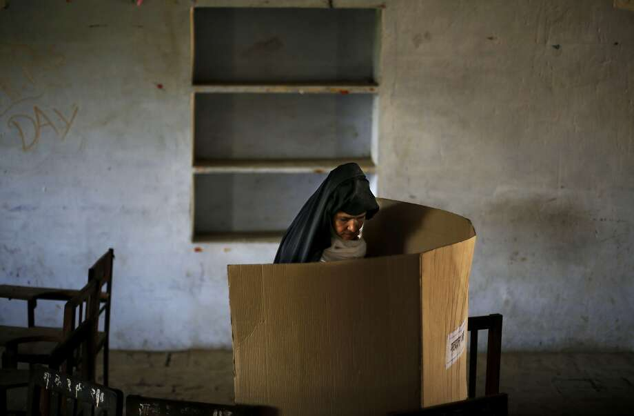 An Indian woman casts her vote at a polling booth in Shahpur village in Muzaffarnagar, in the northern Indian state of Uttar Pradesh, Thursday, April 10, 2014. Indians voted in the crucial third phase of national elections Thursday, with millions going to the polls in the heartland states that are essential to the main opposition Hindu nationalist party's bid to end the 10-year rule of Congress party. (AP Photo/Altaf Qadri) Photo: Altaf Qadri, Associated Press