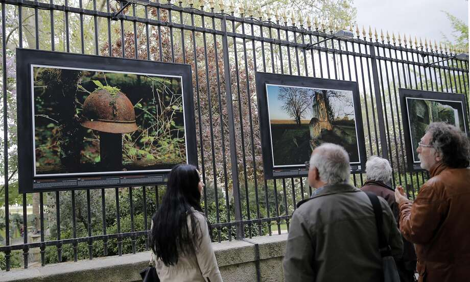 "Visitors look at photos in the exhibit ""Fields of Battle - Lands of Peace 14-18"" at a public park in Paris. Photo: Christophe Ena, Associated Press"