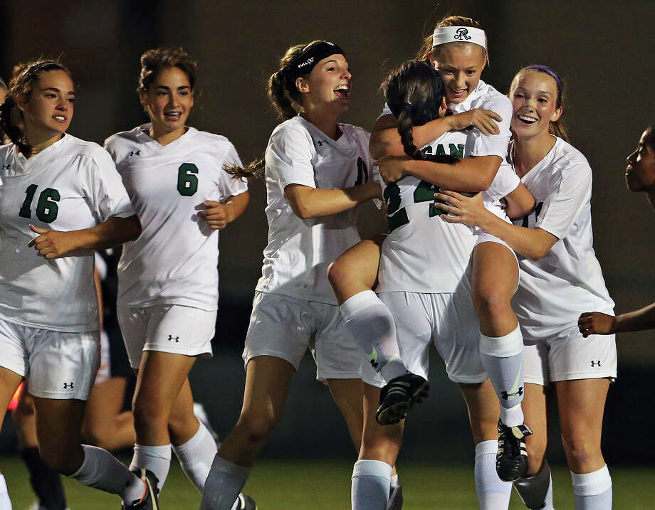 Rattler player Taylor Olson is embraced by teammates after scoring as Reagan plays Steele in 5A regional quarterfinal girls soccer at Blossom West Soccer Stadium on April 8, 2014. Photo: TOM REEL, San Antonio Express-News / San Antonio Express-News